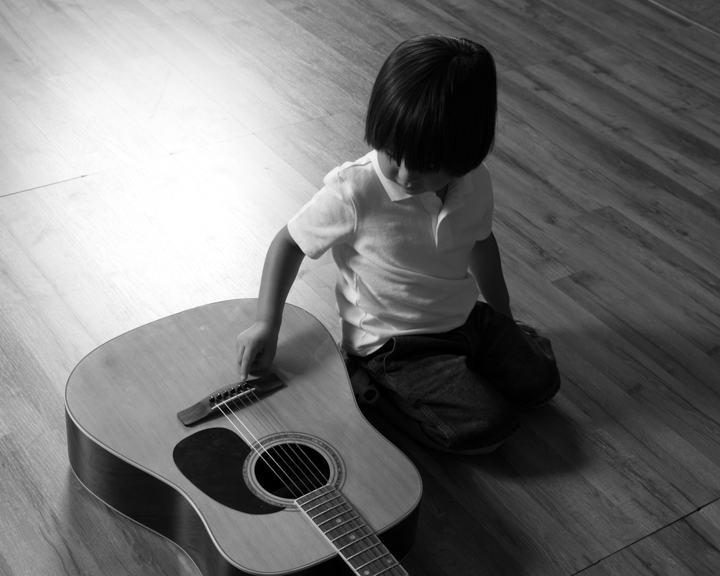 child with guitar black and white photography